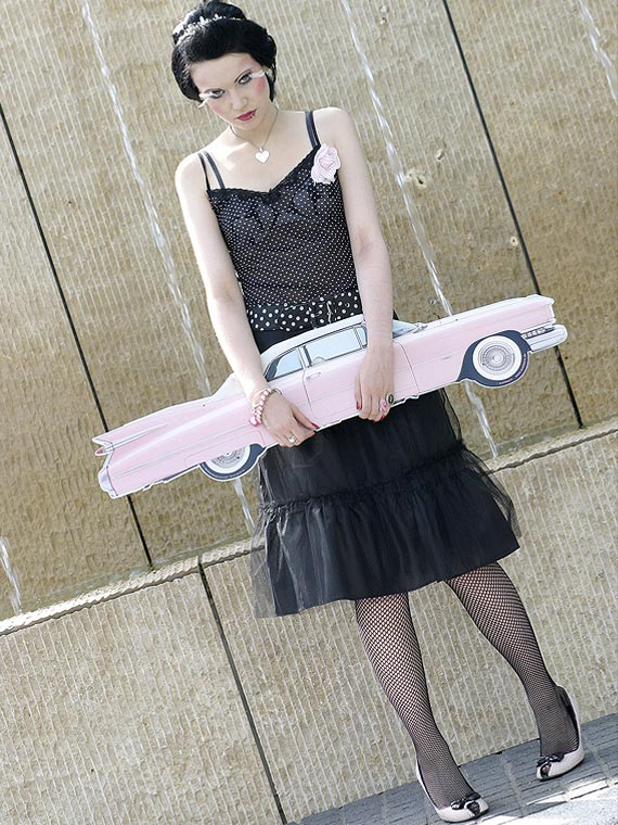 Girl in Fifties-style with pink Cadillac